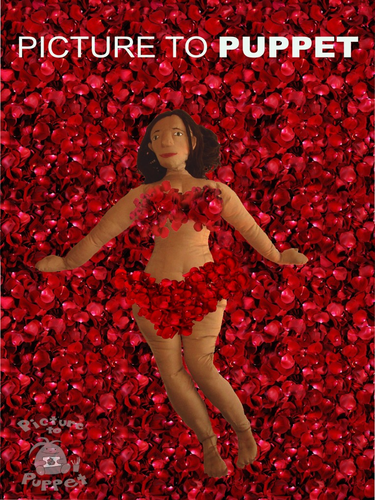 Josie covered in rose petals in a manner resembling the poster for American Beauty.
