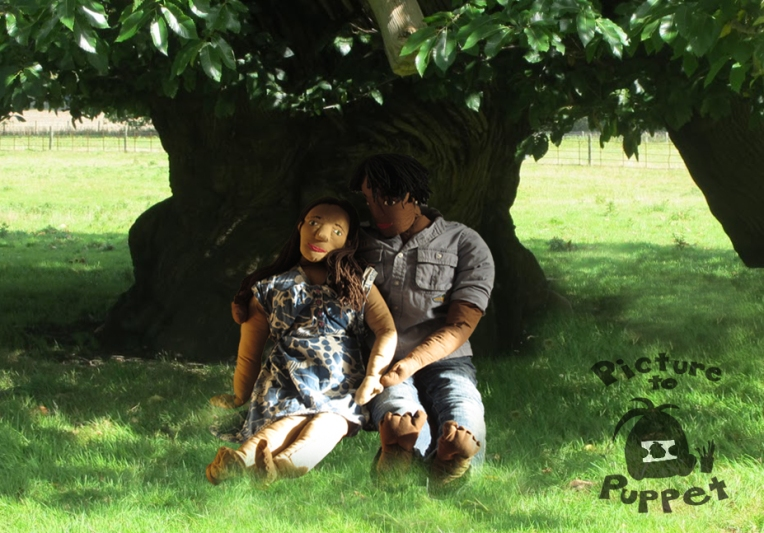 A puppet man, Tim, and a puppet woman, Josie, sit together under a tree.